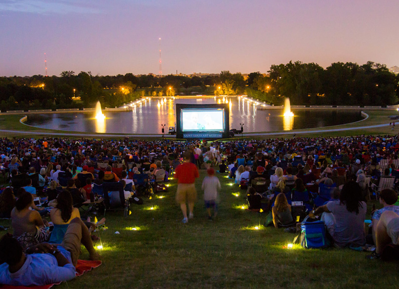 a large crowd on a hill watching a movie outside at sunset