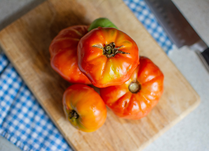 a pile of heirloom tomatoes on a wood cutting board