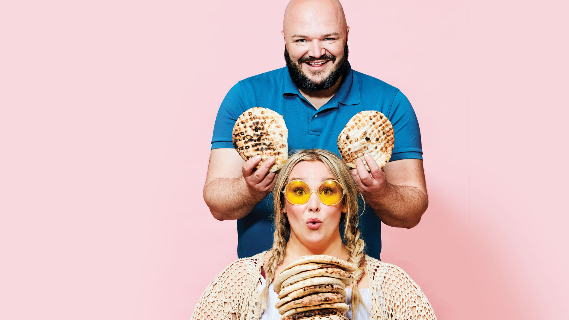 a woman in yellow sunglasses and a man holding up pita up behind her head