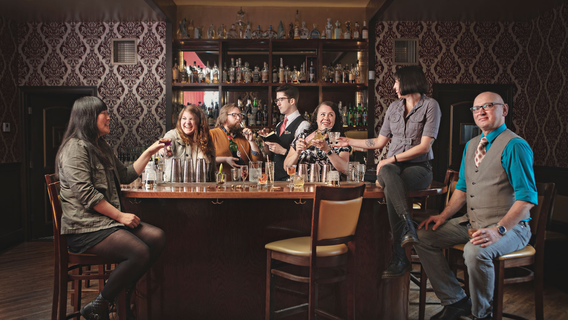 a group making and sharing drinks at a bar while a man in a vest sits on a bar stool in the corner