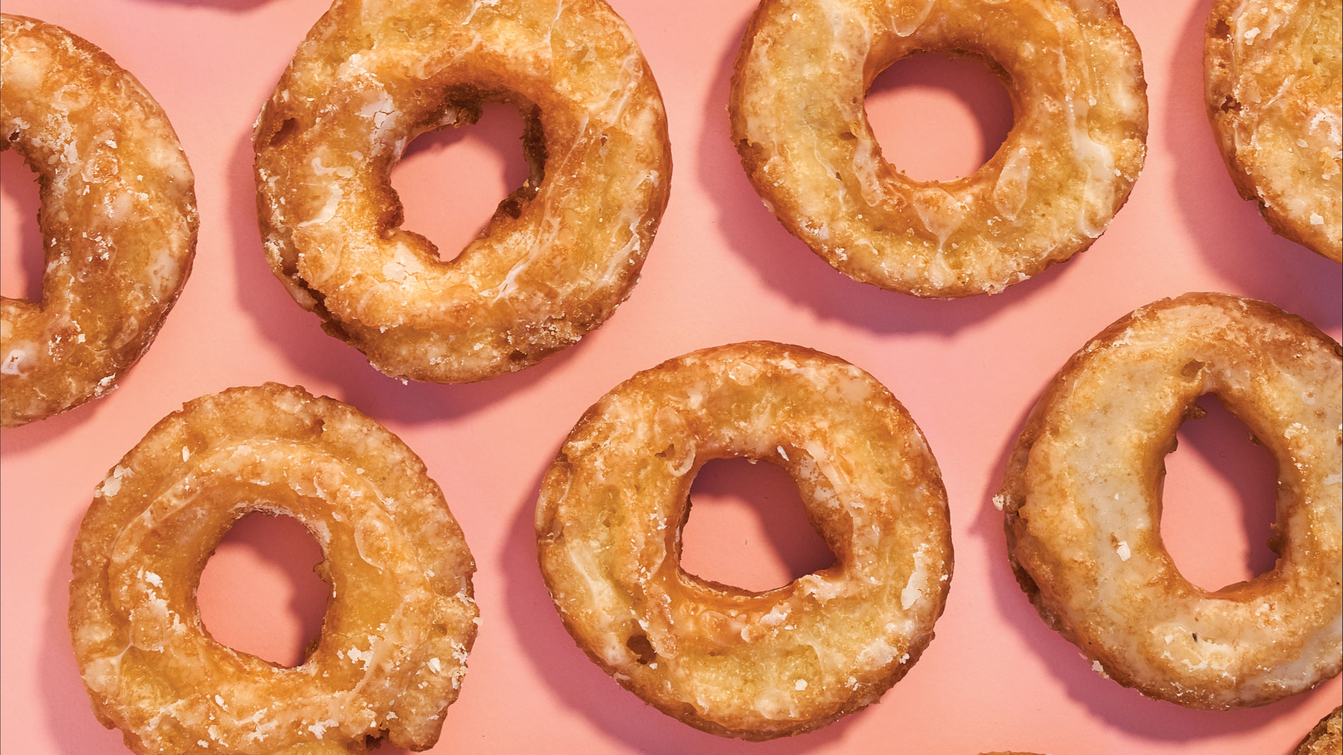 several glazed doughnuts on a pink background