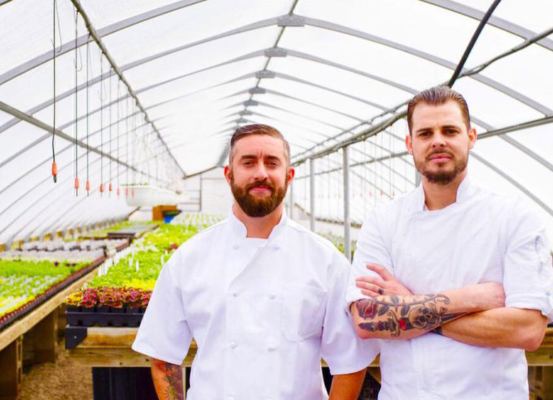 two men in white chefs coats standing in a green house