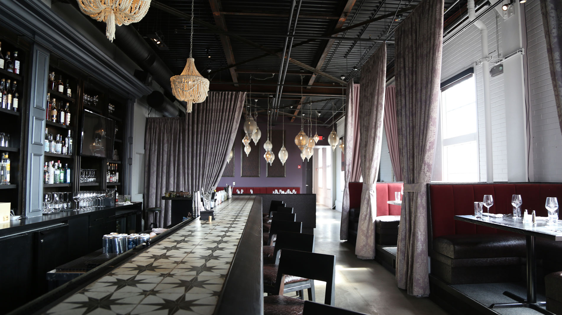 a dark empty elegant restaurant bar with drapes and lanterns