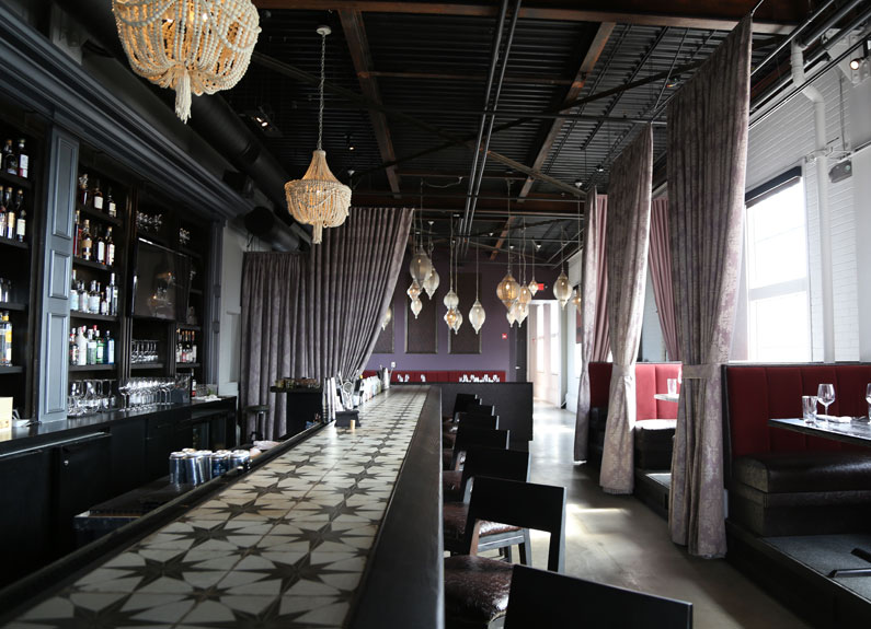 a dark empty elegant restaurant bar with drapes and lanterns