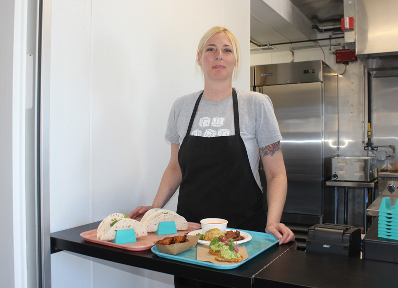 a blonde woman in a black apron carrying a tray of food