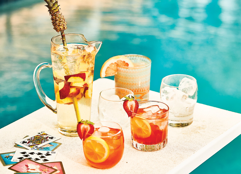 several drinks and a pitcher on a white diving board over a teal pool