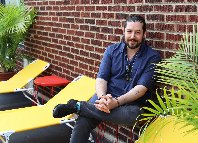 a smiling bearded man sitting on a yellow chair on a patio