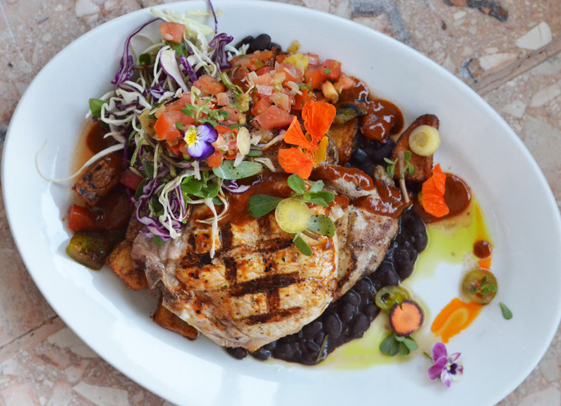 a grilled pork chop topped with colorful flower garnishes