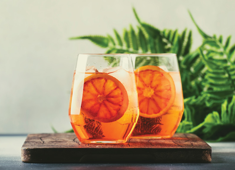 two stemless wineglasses with orange aperol spritzes