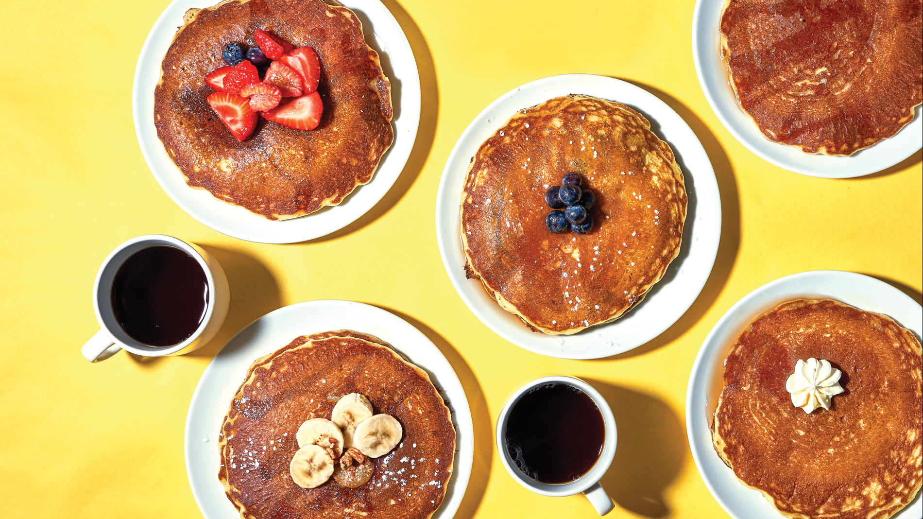 stacks of pancakes and cups of coffee on a yellow background