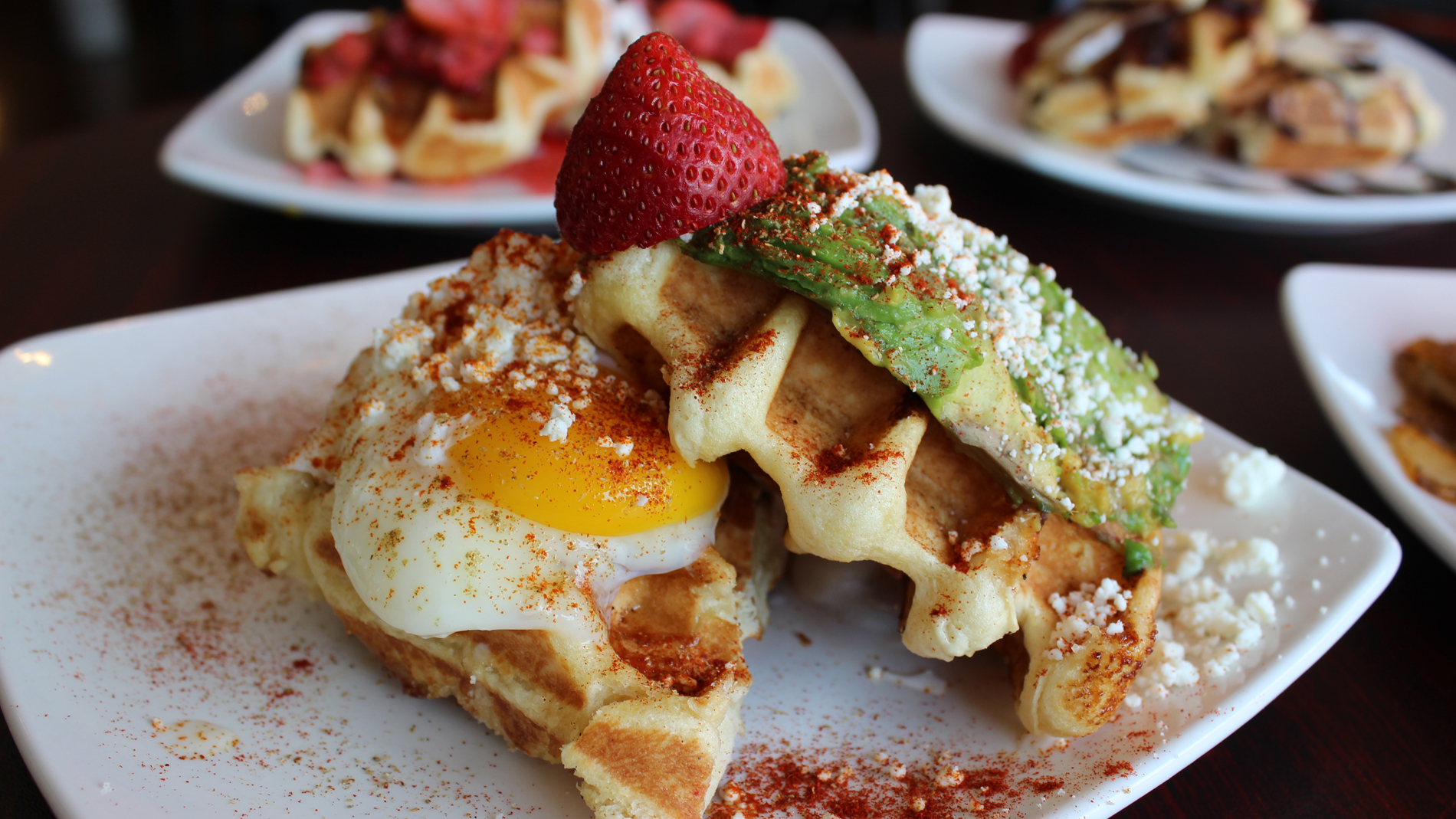 a waffle with avocado and an overeasy egg