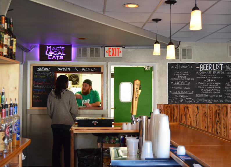 a man at a food window at a bar