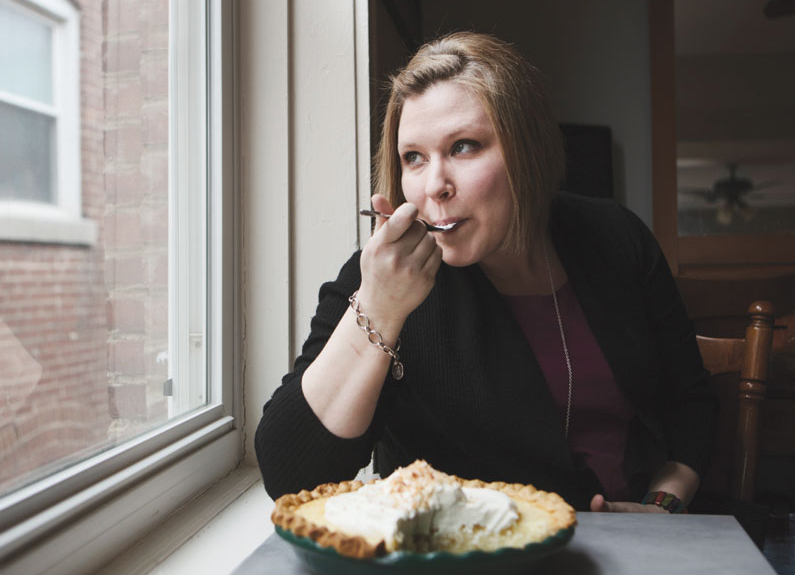 a woman sitting at window eating pie
