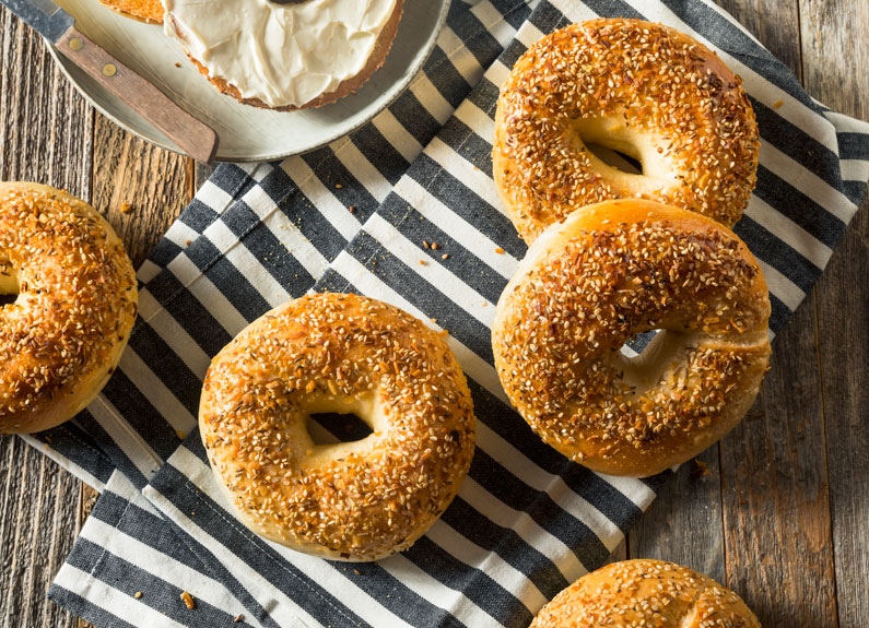 four sesame seed bagels on blue-striped towel