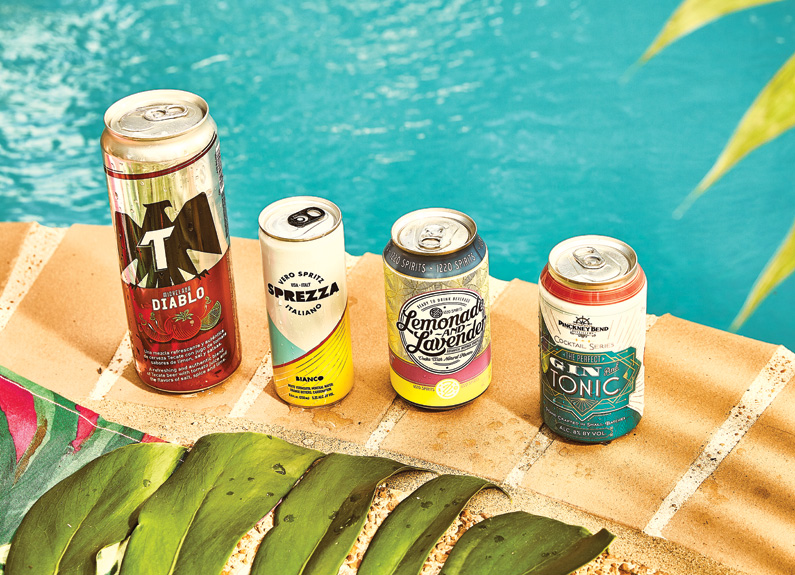 four canned cocktails on the side of a swimming pool