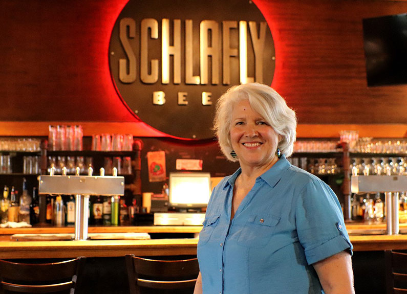 a smiling woman in front of a bar with beer tap handles