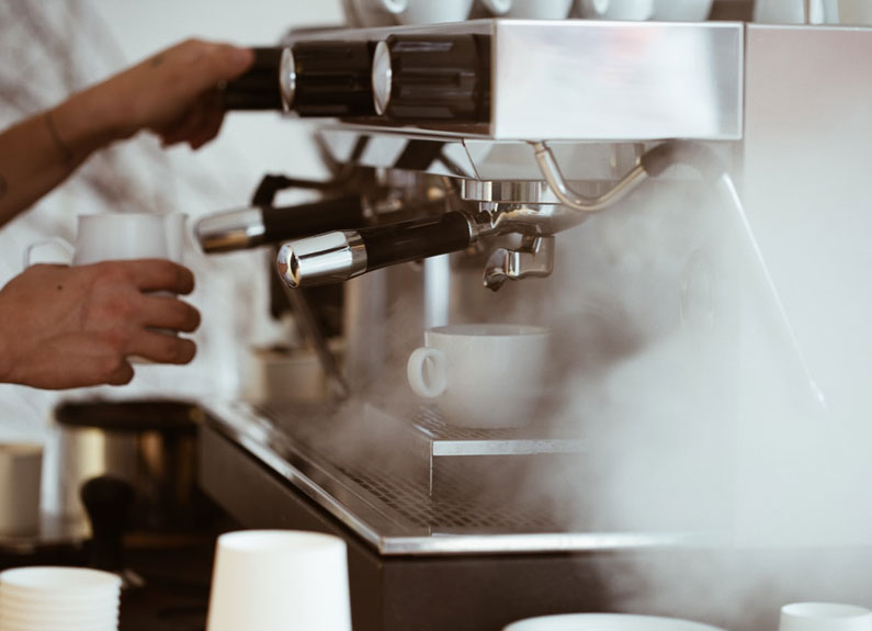two hands at a steaming espresso machine