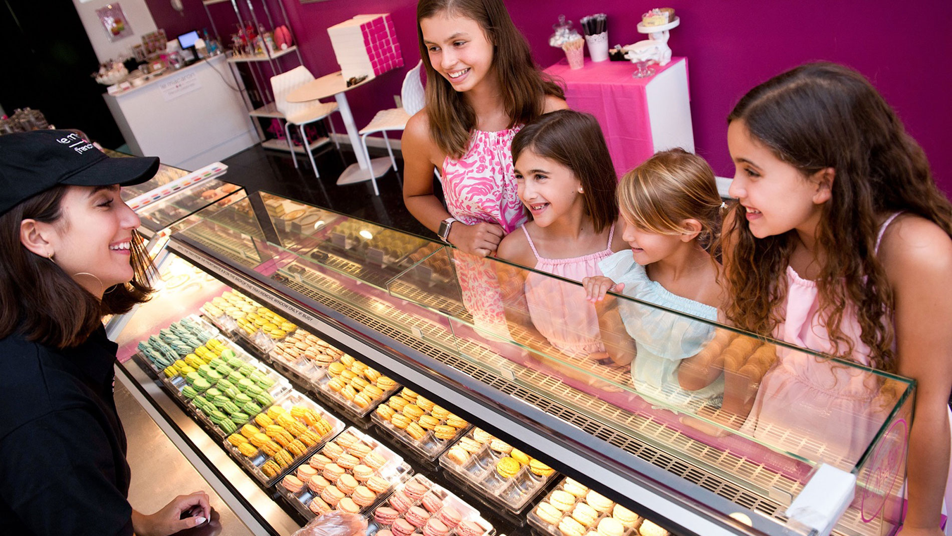 a woman behind a counter helping children select macarons