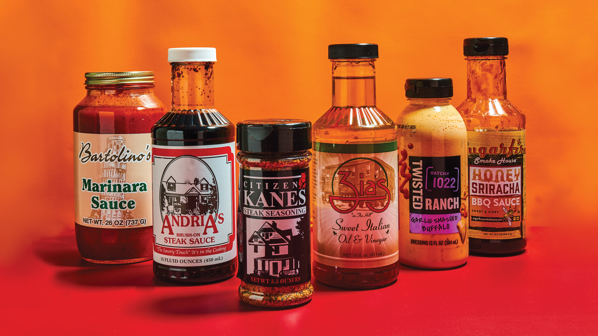 bottles of sauces and rubs on a fiery background