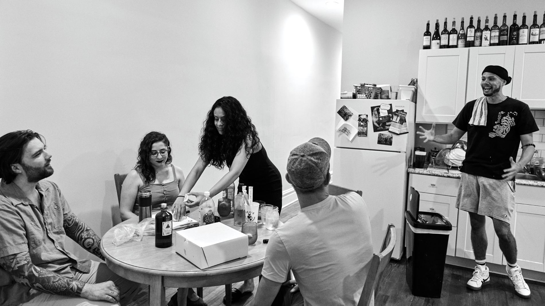 a crowd of people in an apartment kitchen laughing