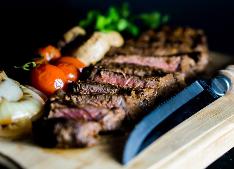 a sliced steak on a board with large steak knife and vegetables