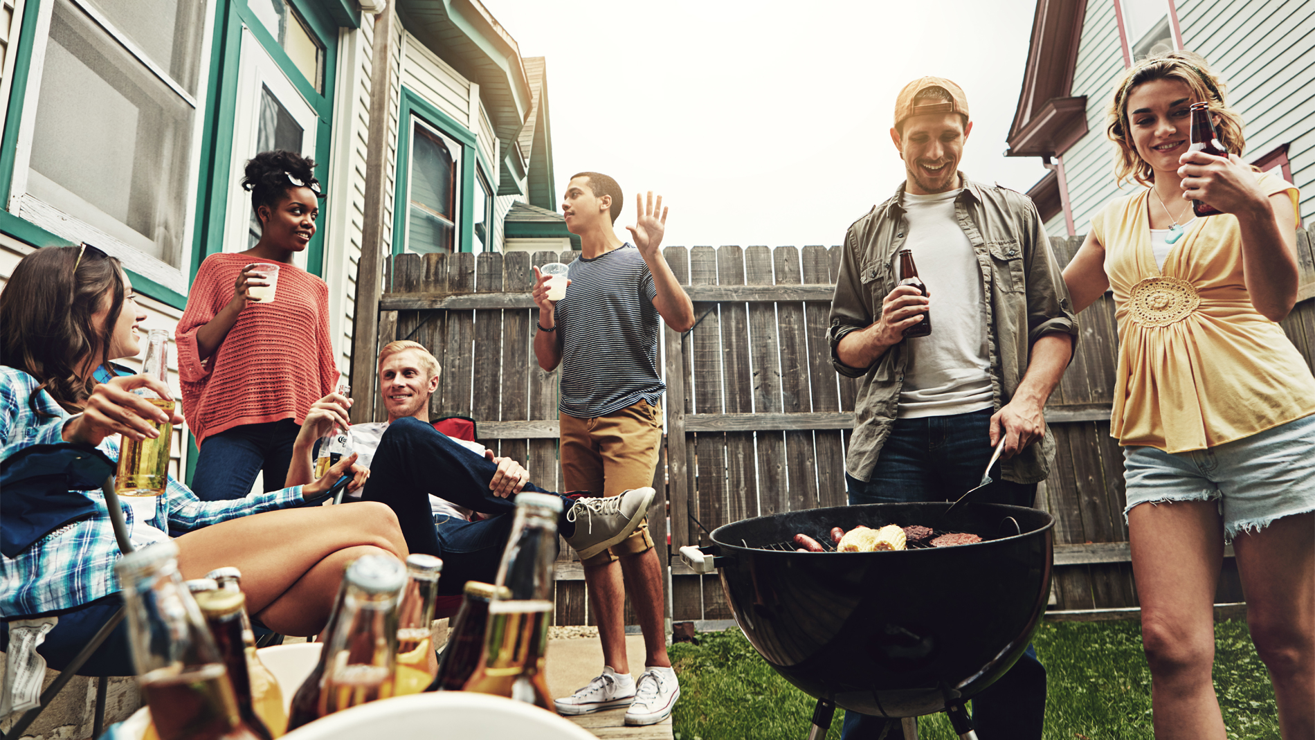 a group of people drinking beer around a grill