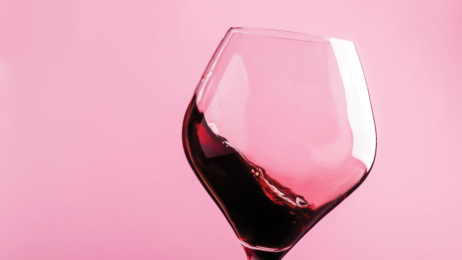 a glass of red wine on a pink background