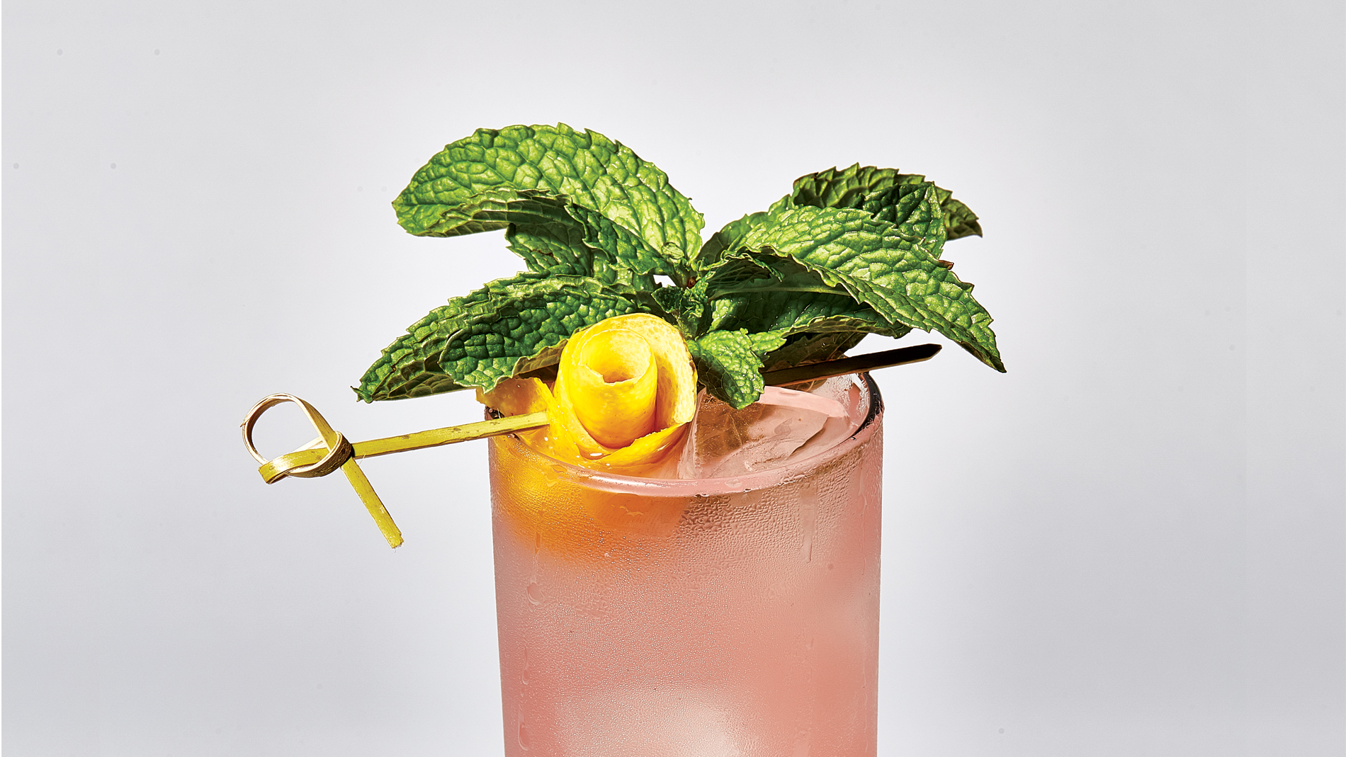 a pink cocktail with a sprig of mint