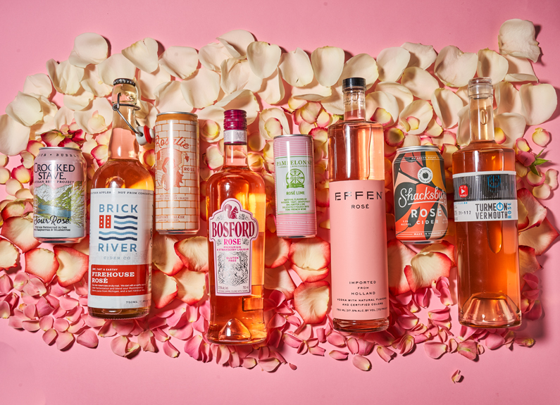 several bottles and cans of rose drinks on a bed of rose petals