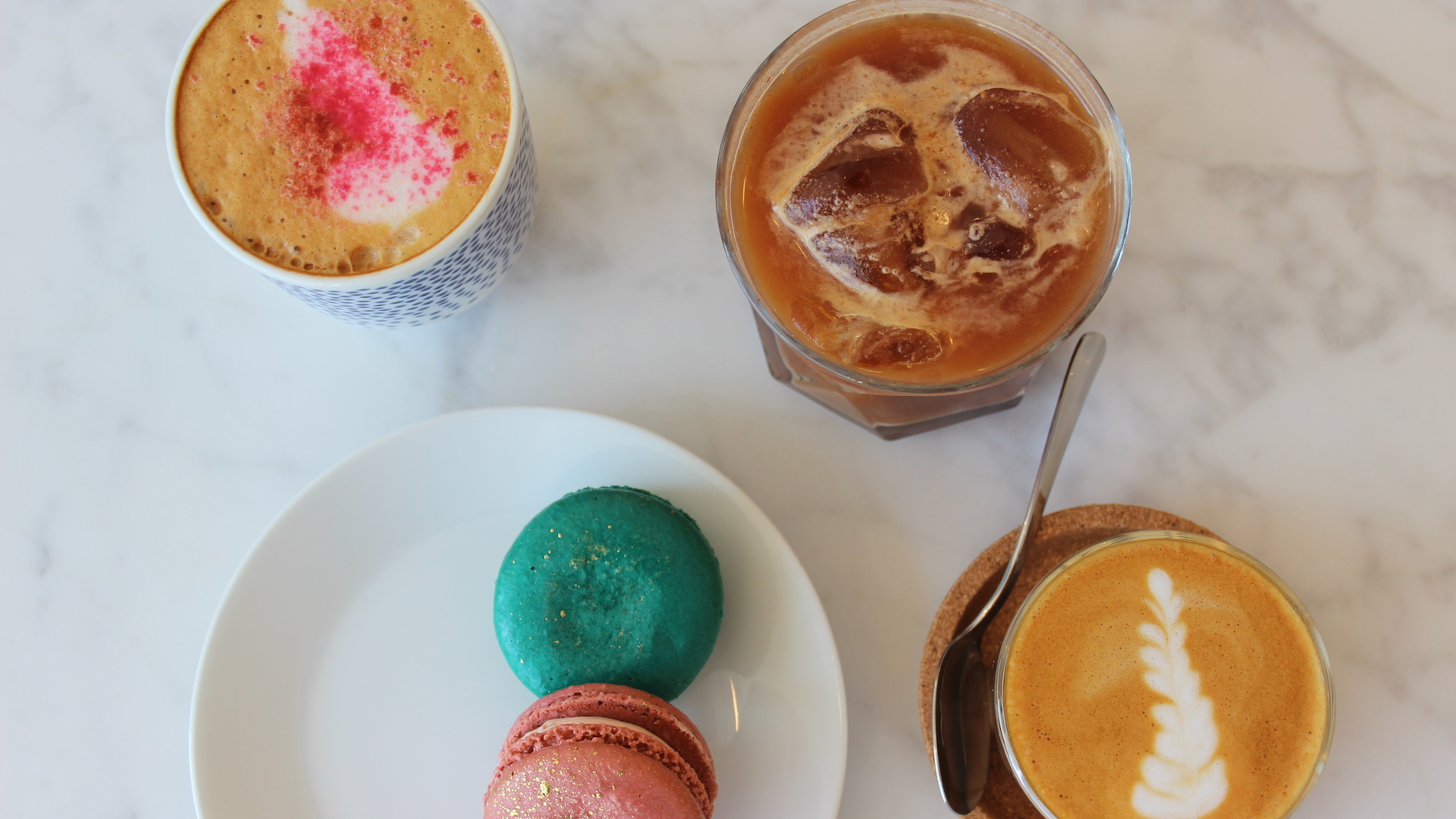 three coffee beverages and two macarons