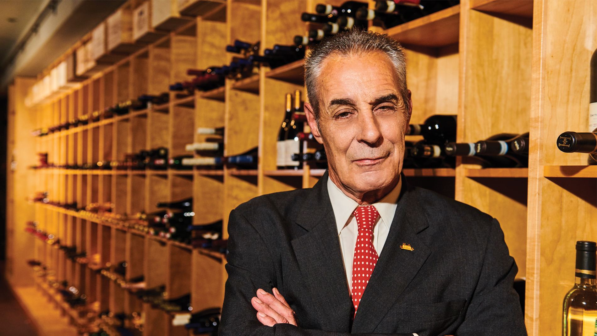 a man in a suit crossed arms standing in front of a wall of wine