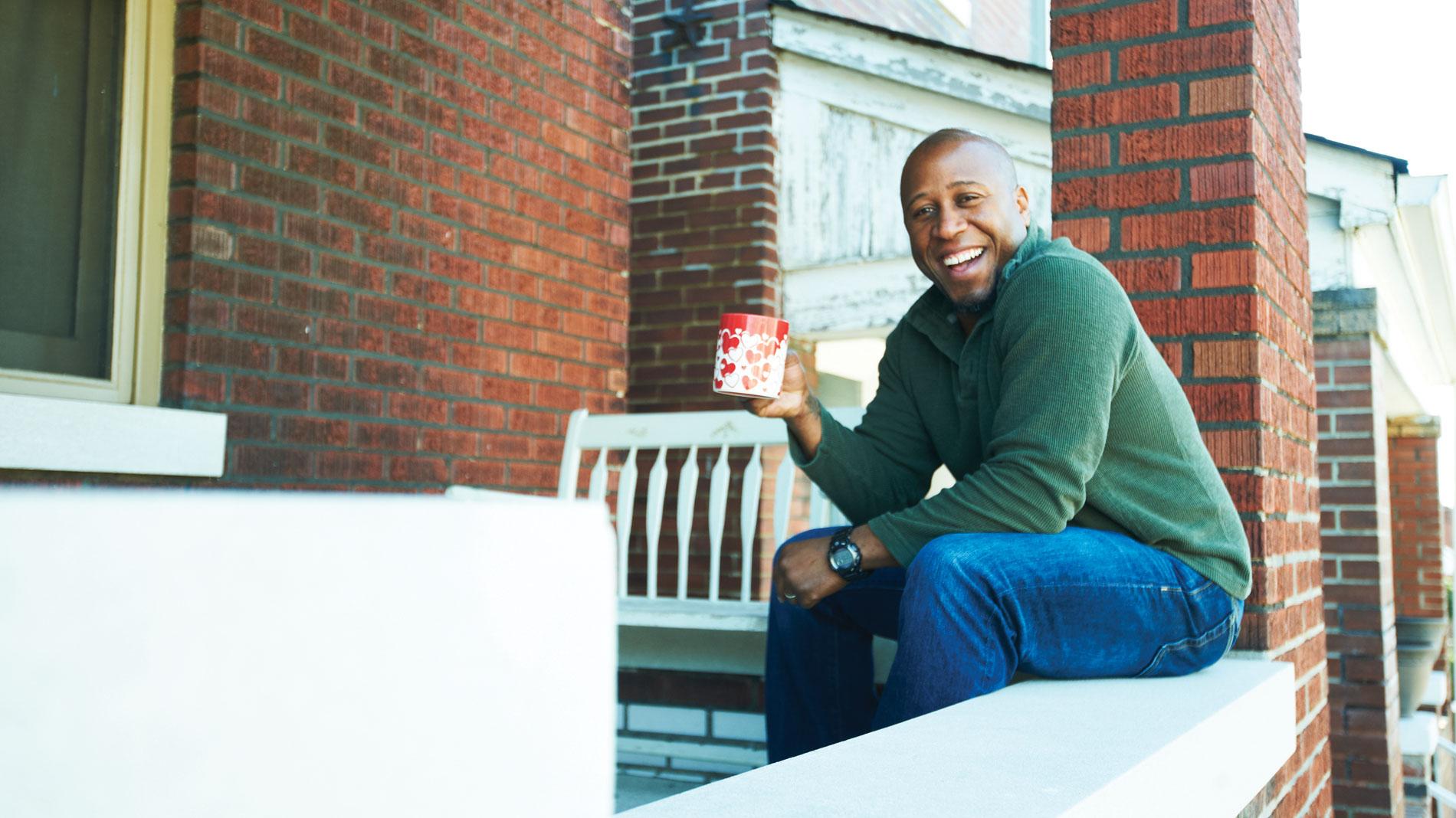 a man holding a mug and sitting on a brick ledge