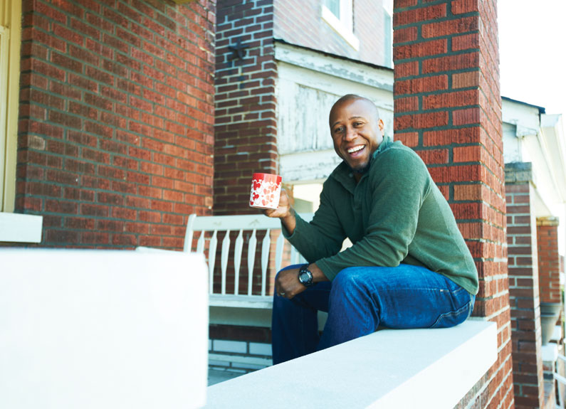 a man holding a mug and sitting on a brick ledge