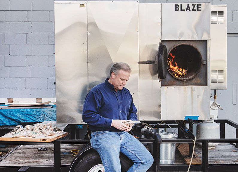a man sitting next to an industrial bbq smoker