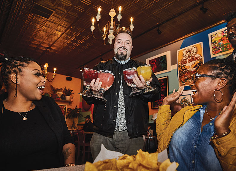 a man serving margaritas to two smiling women