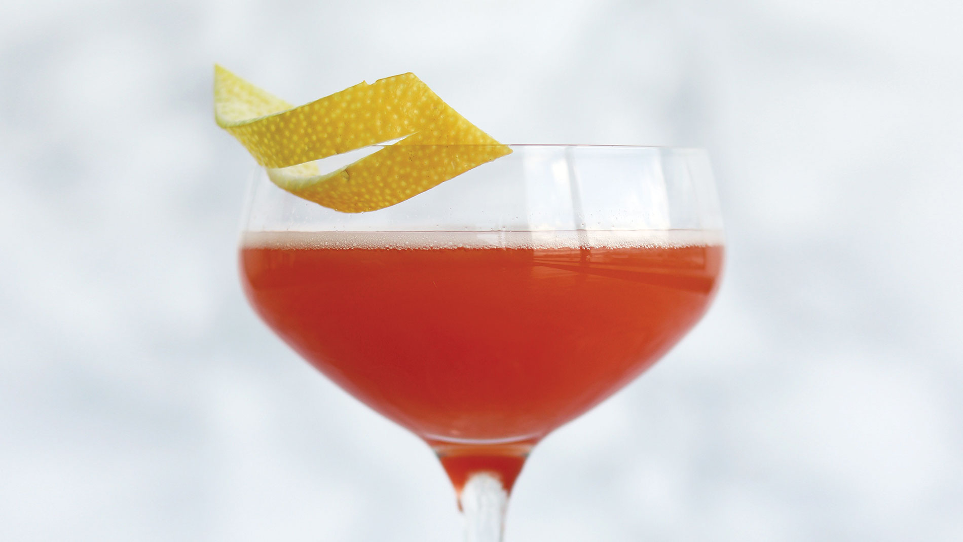 a burnt orange cocktail in a coupe glass with a lemon garnish