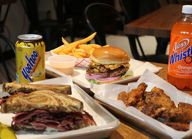 burgers, sandwiches and chicken wings on metal trays with sodas