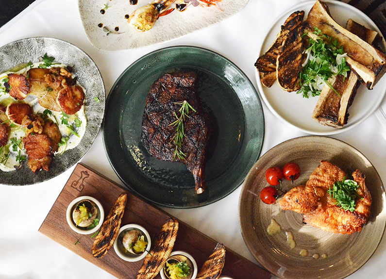 a steak surrounded by several dishes