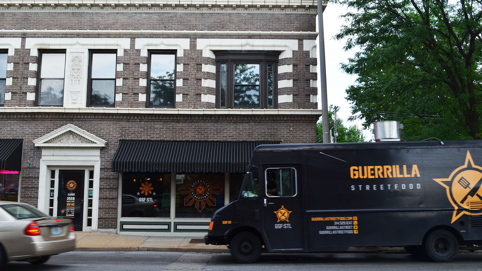 the exterior of a brick building with a food truck in front