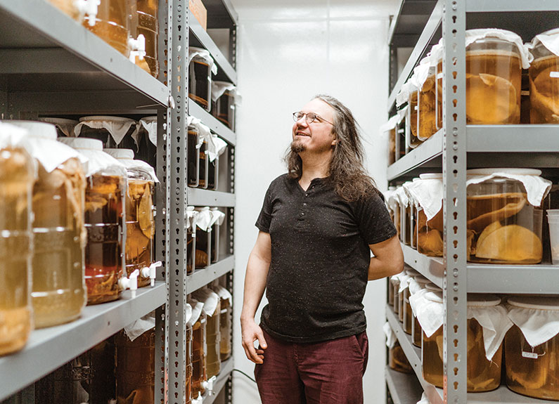 a man walking through shelves of kombucha