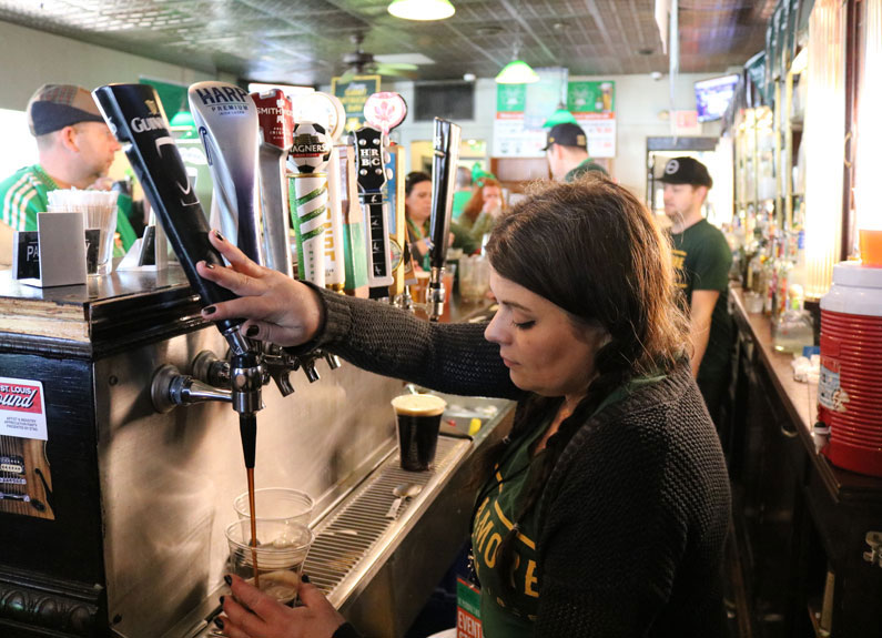 a woman pouring a beer from a tap