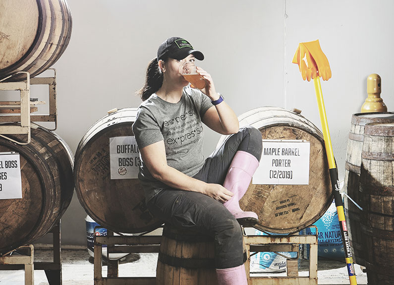 a woman in pink boots drinking a beer while sitting on a barrel