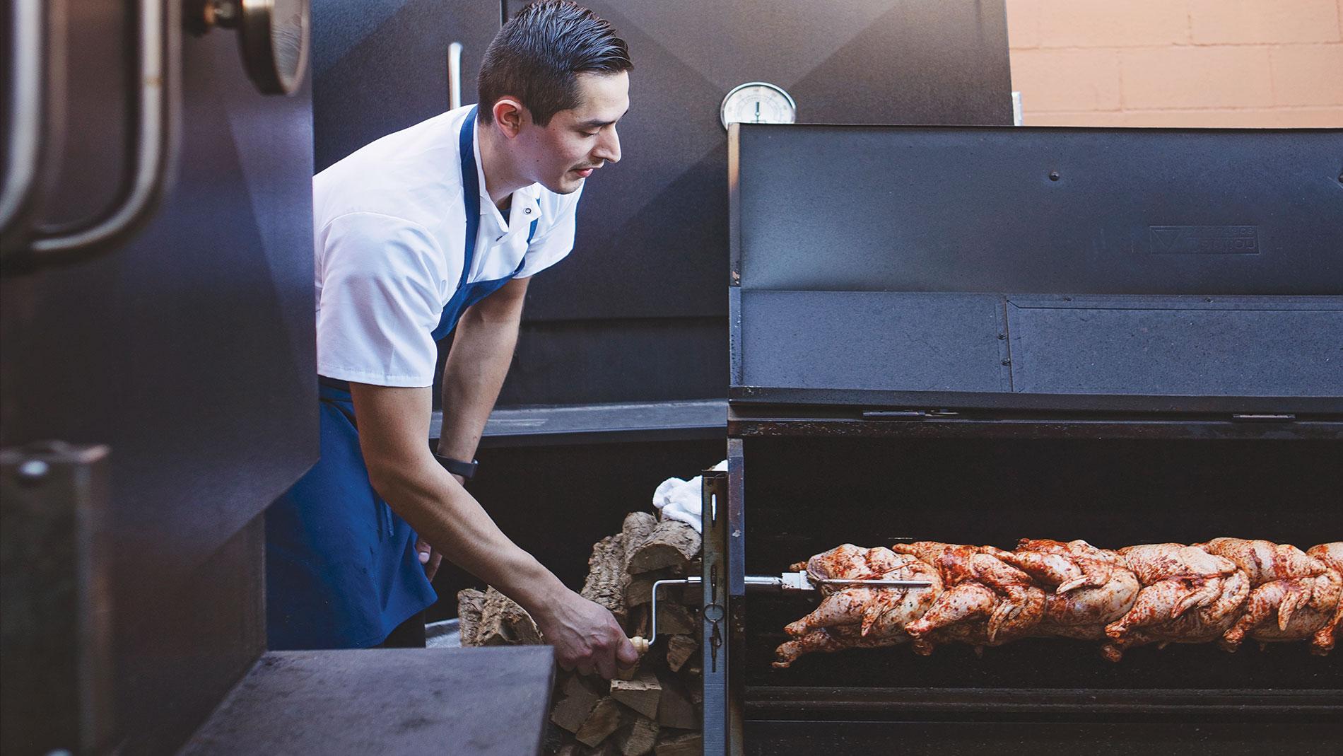 andrew enrique cisneros works on his brasas de pollo, a peruvian rotisserie-style chicken