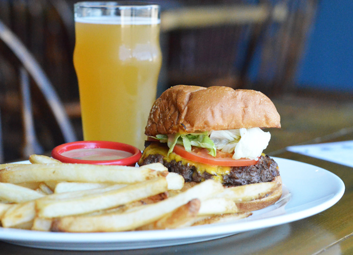 The Classic Brew Cheeseburger is topped with American cheese, lettuce, tomato, onion and the house Signature Wheel fry sauce.