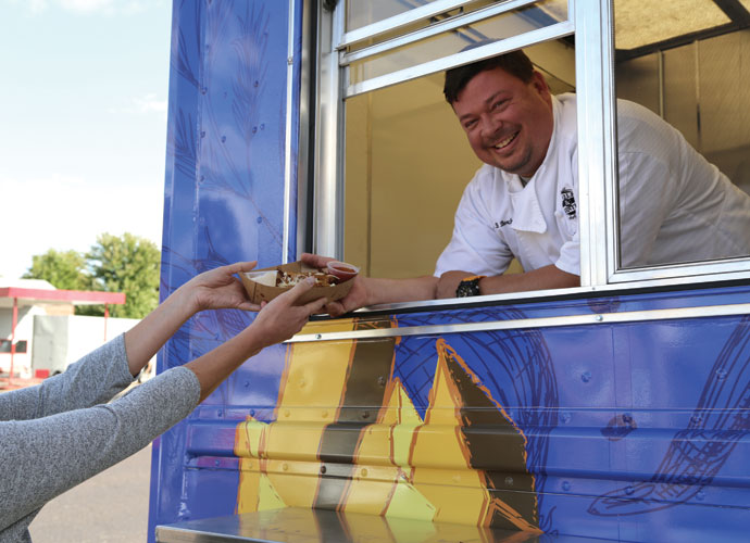 Essentially Fries owner Matt Borchardt passes a basket to hungry hands.