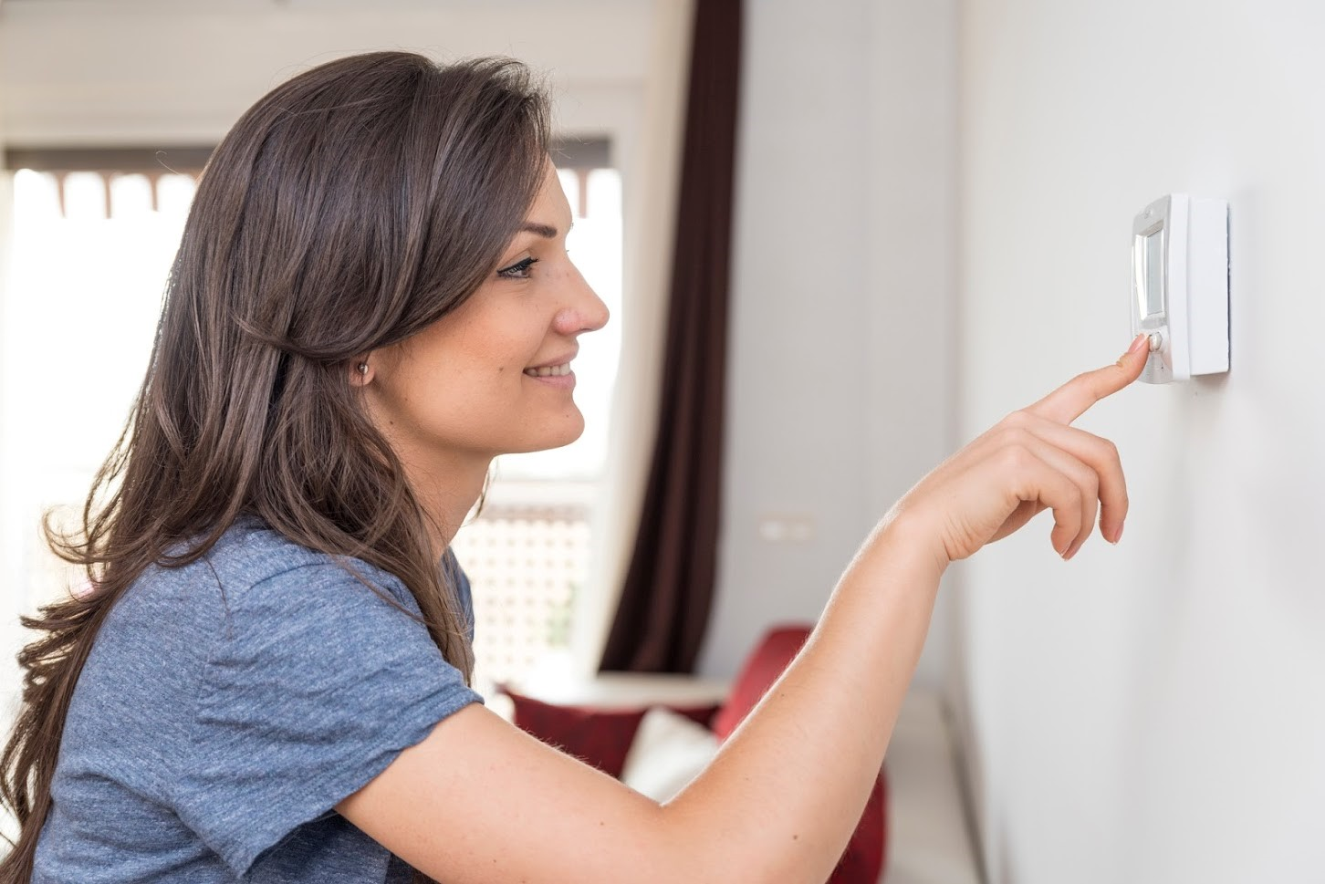 woman using energy efficiency thermostat