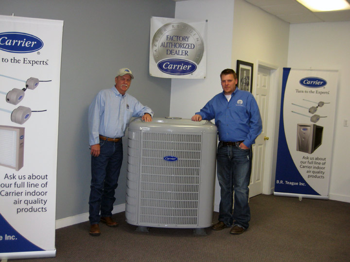 Both owners of Blue Ridge Heating and Air Conditioning standing next to Carrier AC unit