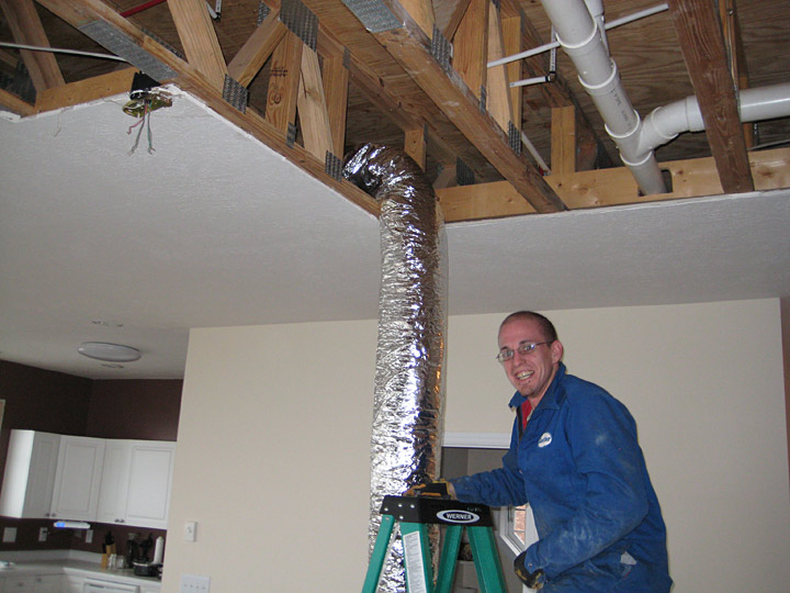 Blue Ridge Heating and Air Conditioning installer working in ceiling on ductwork