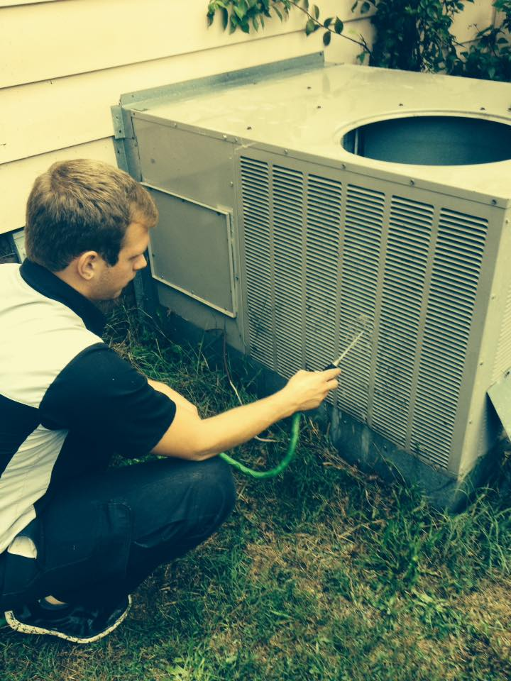 serviceman cleaning outdoor AC unit