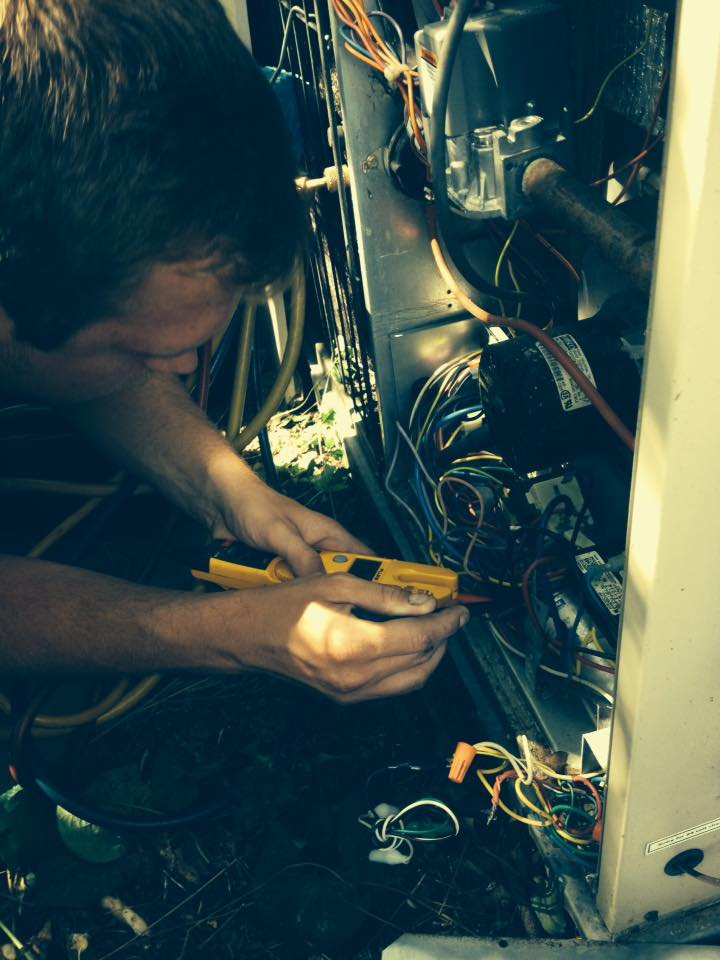 serviceman testing an outdoor condenser unit